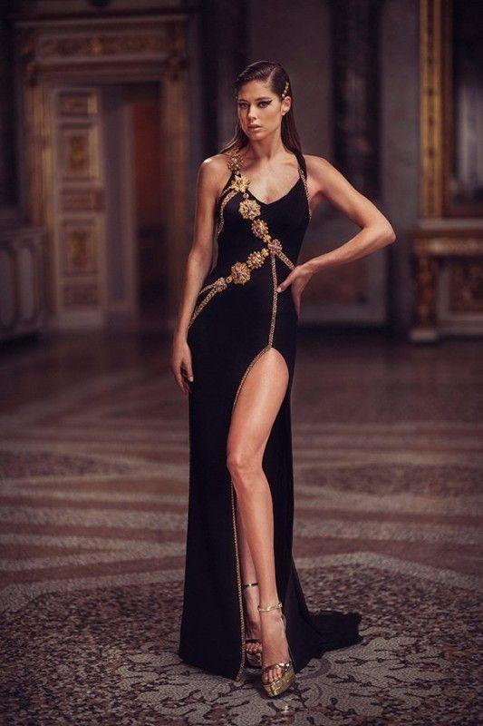 Черное минималистическое вечернее платье с золотистым декором и вырезом на ноге в сочетании с золотыми босоножками на платформе и каблуке с открытым носом и тонким ремешком.