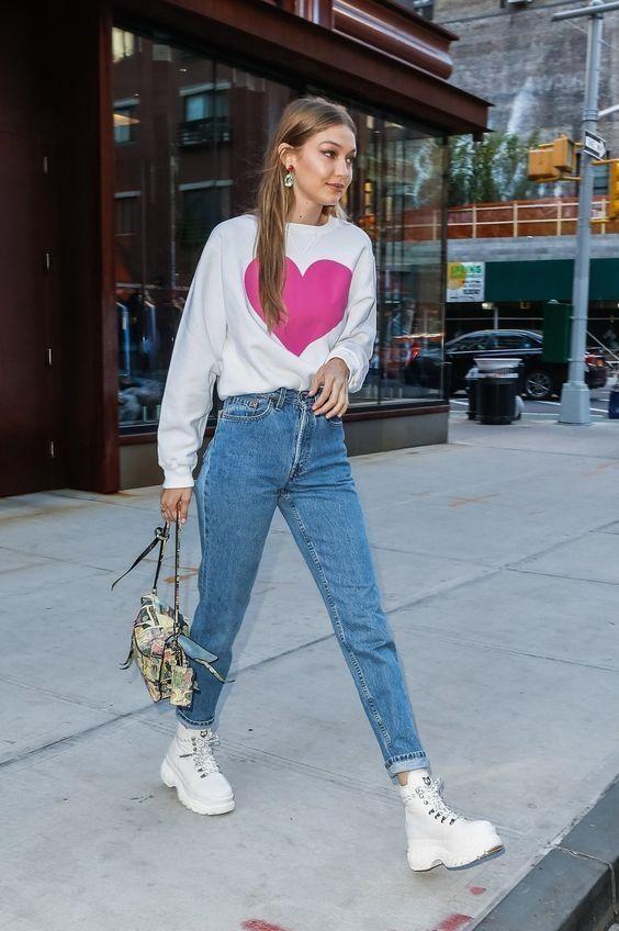 На девушке голубые джинсы мом, белый свитер с рисунком, белые ботинки на шнуровке и платформе.