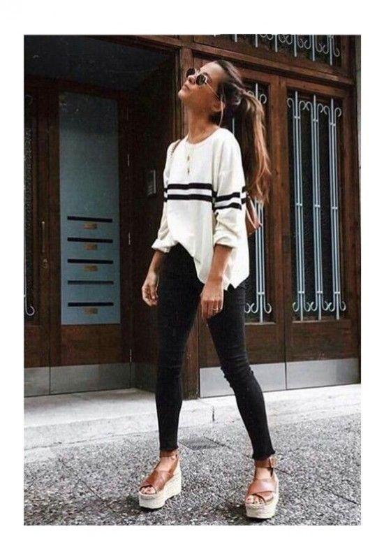 Девушка выбрала длинный белый свитер с черными полосками, черные джинсы-скинни и коричневые туфли на высокой сплошной платформе.