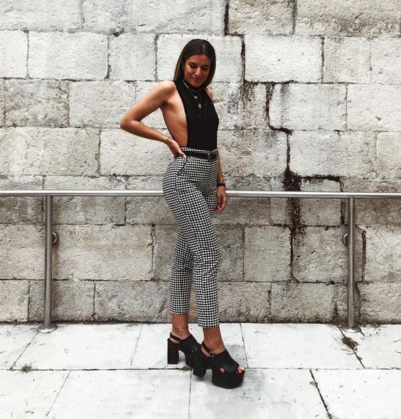 На девушке черная открытая блузка, клетчатые классические брюки туфли на высокой платформе и толстом каблуке, с открытым носком и пяткой.