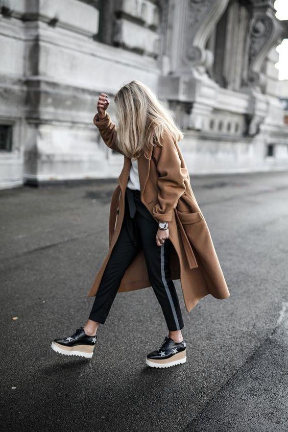 На девушке белая футболка, черные брюки с серой полоской, кашемировое коричневое пальто длины миди свободного кроя и черные туфли на шнуровке с коричнево-белой высокой танкеткой.