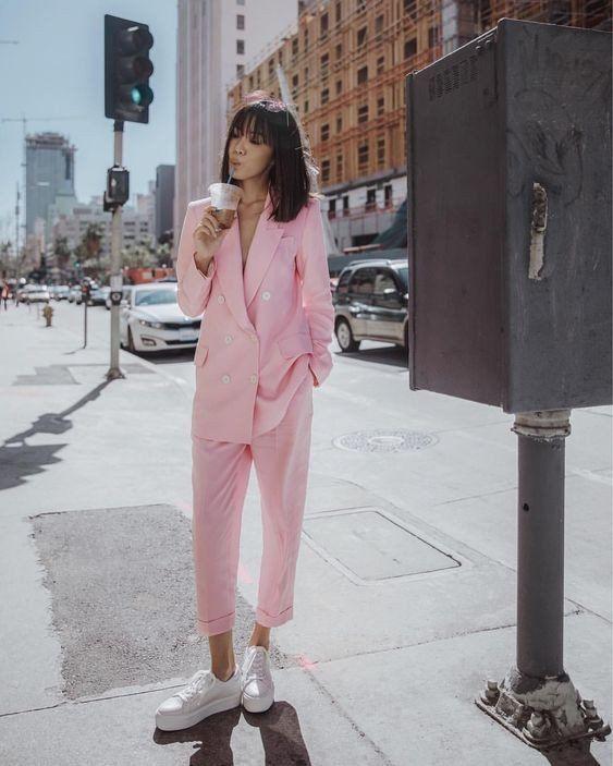 На девушке нежно-розовый брючный костюм в сочетании с белыми туфлями на шнуровке и толстой подошве.