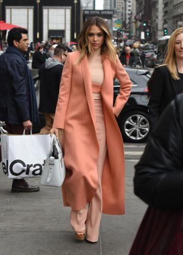 На девушке светло-персиковый костюм с удлиненными брюками, персиковое пальто свободного кроя и светло-коричневые туфли на платформе с открытым носом.