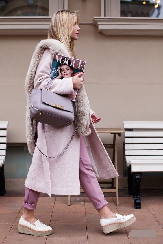 На девушке фиолетовые брюки с отворотами, лиловое пальто свободного кроя с мехом, белые туфли на танкетке и фиолетовая сумка.