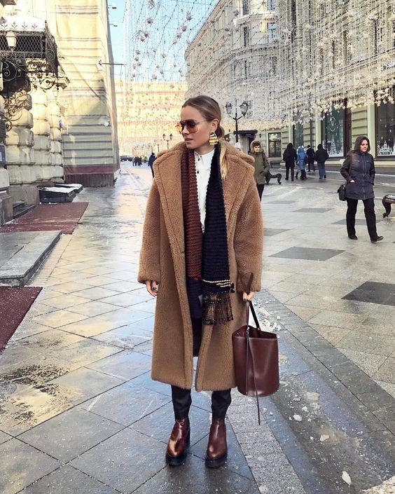 На девушке белая рубашка, коричнево-черный шарф, теплое пальто, брюки и коричневые ботинки на толстой платформе. Образ дополнен очками и сумкой.