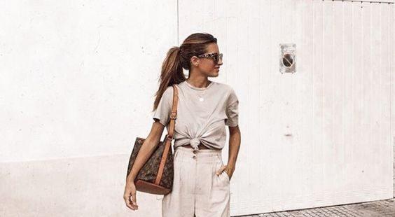 Светло-коричневая футболка, завязанная на поясе, бежевые свободные брюки в сочетании с туфлями на шнуровке и высокой белый платформе.