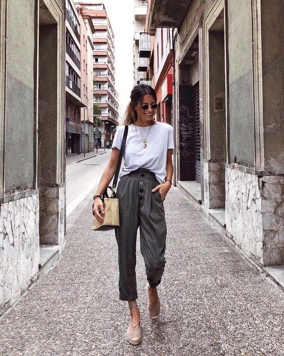 Девушка надела однотонную белую футболку, темно-зеленые брюки свободного кроя, бежевые туфли на сплошной платформе с переплетами на щиколотке. Образ дополняют очки и поясная сумка.