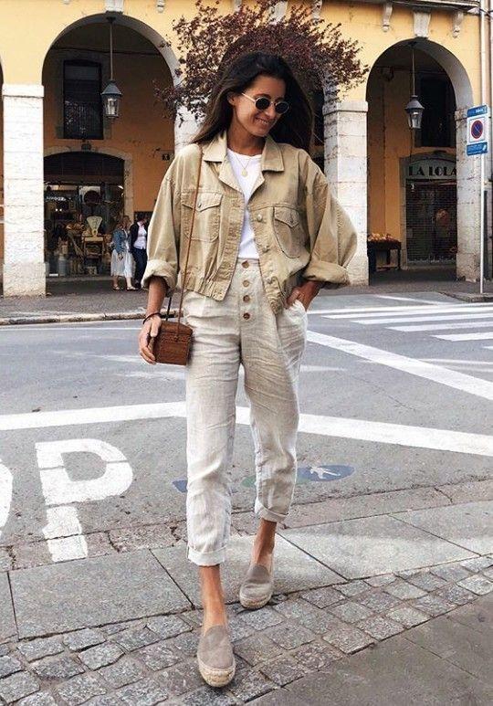 На девушке белая футболка, бежевая куртка, хлопковые белые летние брюки и тканевые туфли на сплошной платформе. Образ дополнен маленькой веревочной сумкой и очками.