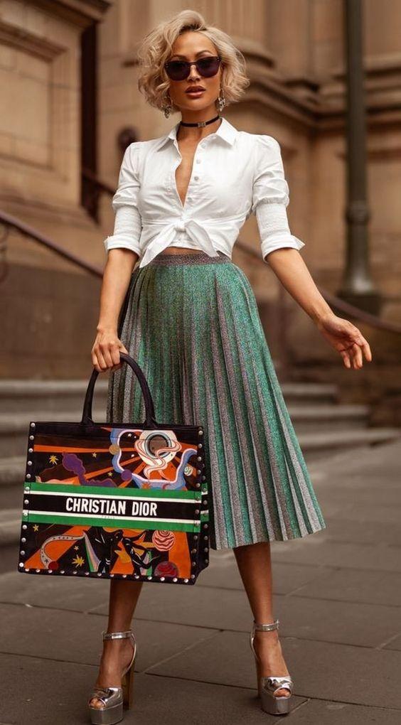 Белая приталенная рубашка, завязанная на поясе, блестящая юбка-плиссе миди и туфли на платформе и высоком каблуке цвета металлик с открытым носом и ремешком, яркая сумка Dior и очки.