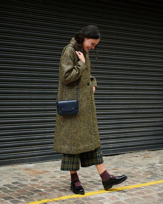 На девушке тускло-зеленое пальто свободного кроя ниже колена, клетчатые зеленые свободные брюки, темно-фиолетовые носки, поясная темно-синяя сумка и туфли Mary-janes на невысокой платформе и каблуке.