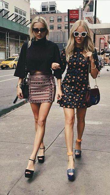 Первая девушка выбрала короткую черную рубашку с свободными рукавами, облегающую юбку-мини, черную поясную сумку и туфли на платформе и каблуке с открытым носом и тонким ремешком. Вторая девушка надела короткое цветочное платье и сине-желтые туфли на платформе и каблуке Образ дополнила поясной сумкой и очками.