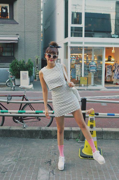 Белый топ в мелкий черный горошек и такой же расцветки облегающая юбка-мини в сочетании с высокими розовыми носками и белыми туфлями на шнуровке и широкой сплошной подошве.