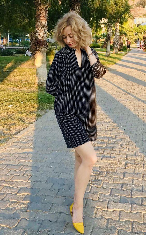 На девушке черное платье-мини в белый горошек свободного кроя и желтые лодочки на низком ходу с заостренным носом.