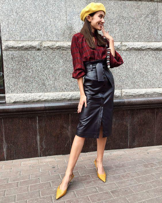 На девушке клетчатая бордовая рубашка с объемными рукавами, черная кожаная юбка-карандаш ниже колена с завышенной талией и поясом, желтые лодочки на невысоком каблуке с заостренным носом, берет такого же цвета.
