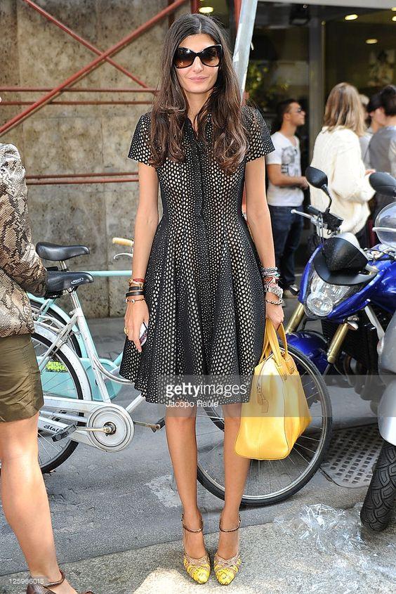 На девушке черное пышное короткое платье в белый горошек, желтая сумка и желтые лодочки с узором.