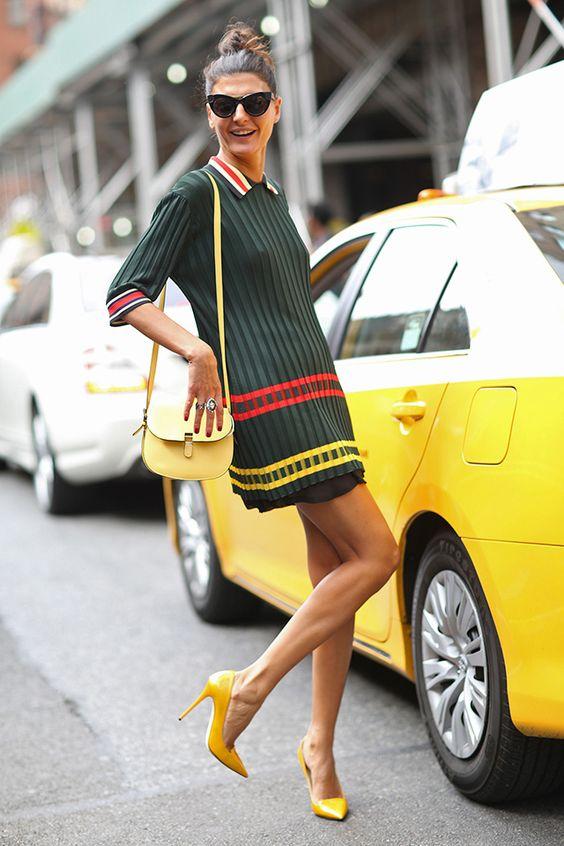 На девушке прямое платье темно-зеленого цвета с красными и желтыми полосками, бледно-желтая поясная сумка и ярко-желтые лодочки на каблуке с заостренным носом.