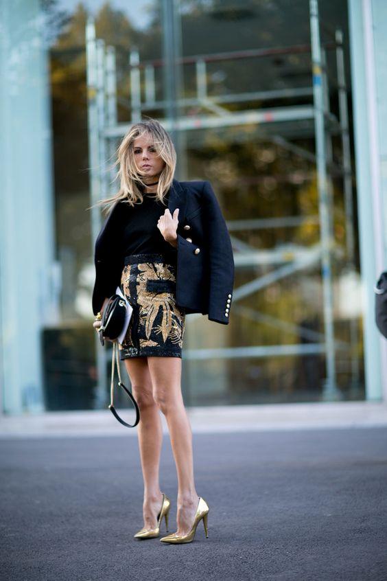 На девушке черный гольф, облегающая юбка-мини с золотистым декором, черный пиджак свободного кроя, сумка и золотистые лодочки на каблуке с заостренным носом.