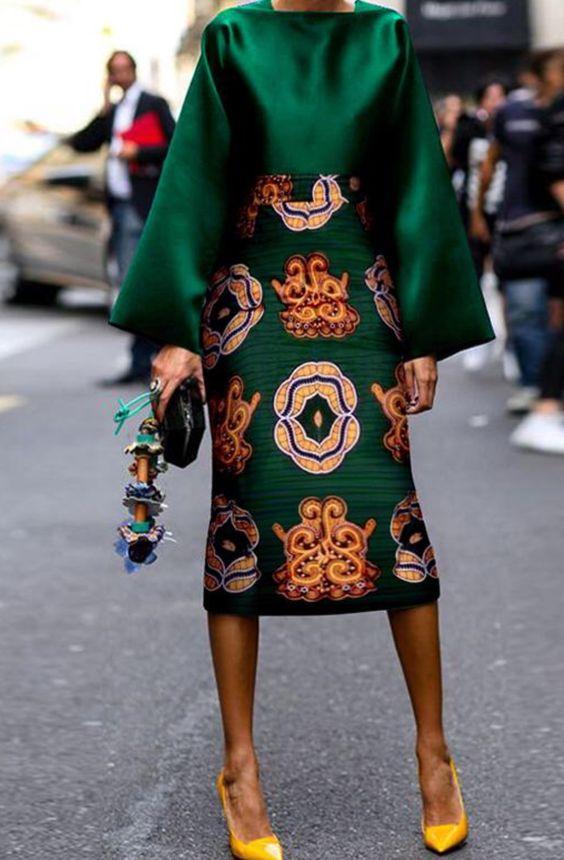Изумрудная однотонная блуза с пышными рукавами, зеленая облегающая юбка-карандаш длины миди с узорами сочетаются с желтыми лодочками.