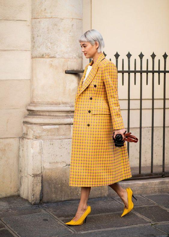 Девушка надела желтое клетчатое пальто свободного кроя длины миди и желтые лодочки на шпильке с заостренным носом.