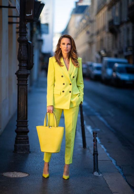 Желтый брючный костюм в сочетании с такого же цвета сумкой и лодочками.