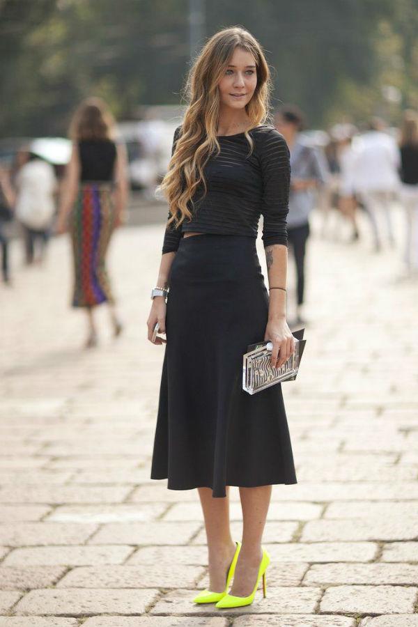 На девушке черный укороченный топ, черная юбка-миди с воланами, клатч и лодочки лимонного цвета на высоком каблуке с заостренным носом.