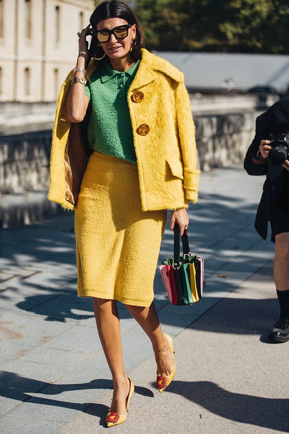 На девушке зеленая футболка с воротником, желтый пиджак с пуговицами, юбка-карандаш, цветная сумка и желтые лодочки.