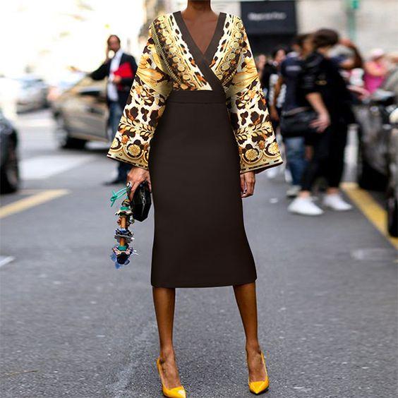На девушке топ с V-образным вырезом, широкими рукавами и ярким золотистым принтом, черная юбка-карандаш с высокой талией ниже колена и желтые лодочки с заостренным носом.