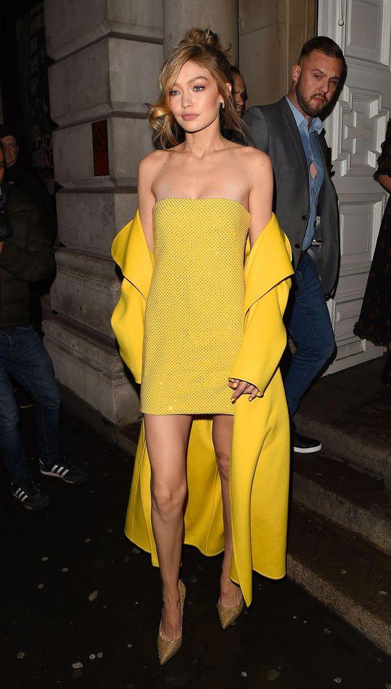 На девушке желтое прямое коктейльное платье с стразами, желтое пальто-миди и золотистые лодочки с заостренным носом.
