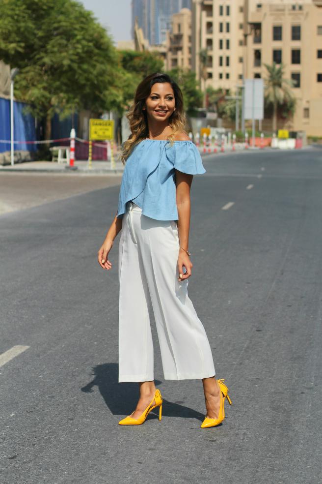 На девушке небесно-голубая блузка со спущенными плечами, белые кюлоты и ярко-желтые лодочки на высоком каблуке с вырезами и бантиком.