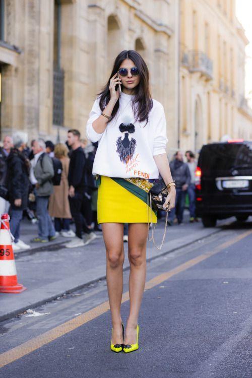 Белый свободный свитер с рисунком, желтая прямая юбка длины мини сочетается с кислотными лодочками на каблуке. Образ дополнен сумкой и очками.
