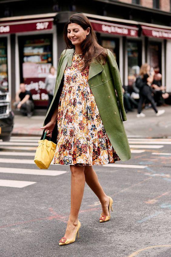 Девушка надела прямое белое  платье с воланами и цветочным принтом выше колена, зеленое кожаное пальто и бледно-желтые лодочки на каблуке с заостренным носом и декоративным красным узором.