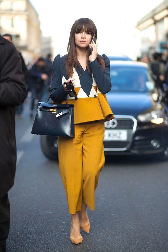 Сине-желтая блуза, свободные гороховые брюки в сочетании с бледно-желтыми замшевыми лодочками и синей кожаной сумкой.
