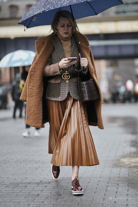 На девушке клетчатый пиджак, подчеркнутый черным поясом, светло-коричневая юбка плиссе длины миди, искусственная шуба в тон к юбке и темно-коричневые дерби.