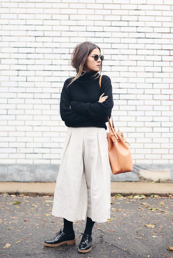 На девушке черный свитер с горлом, белые укороченные брюки-палаццо, черные плотные колготы и лаковые черные оксфорды на коричневой подошве. Образ дополняет бледно-оранжевая сумка и очки.