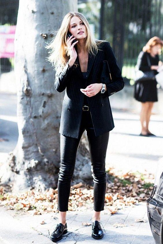 Черный удлиненный пиджак в полоску, облегающие кожаные брюки сочетаются с черными оксфордами. Образ дополняет черный клатч и аксессуары.