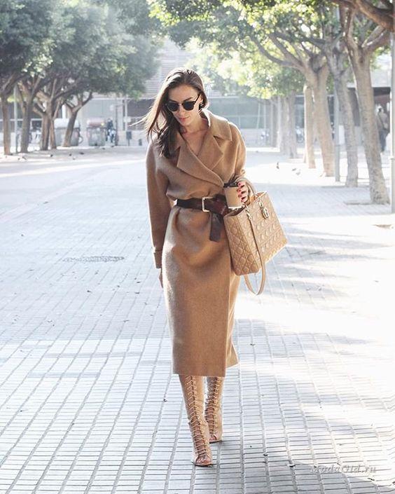 На девушке светло-коричневое кашемировое пальто миди с коричневым кожаным поясом и бежевые высокие туфли на шнуровке. Образ дополнен очками и бежевой сумкой.