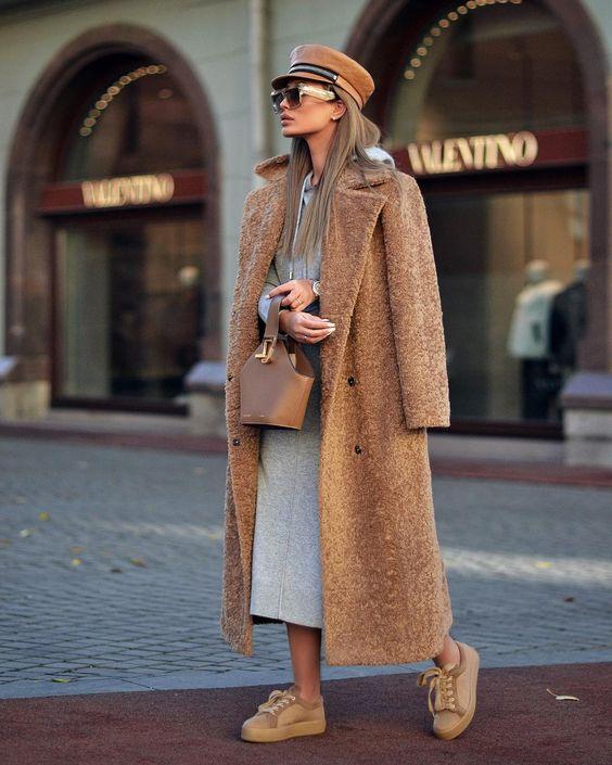 На девушке серое платье-худи прямого кроя длины макси, свободное коричневое пальто и темно-бежевые туфли на шнурках. Образ дополняет коричневый кепи, такого же цвета сумка и очки.