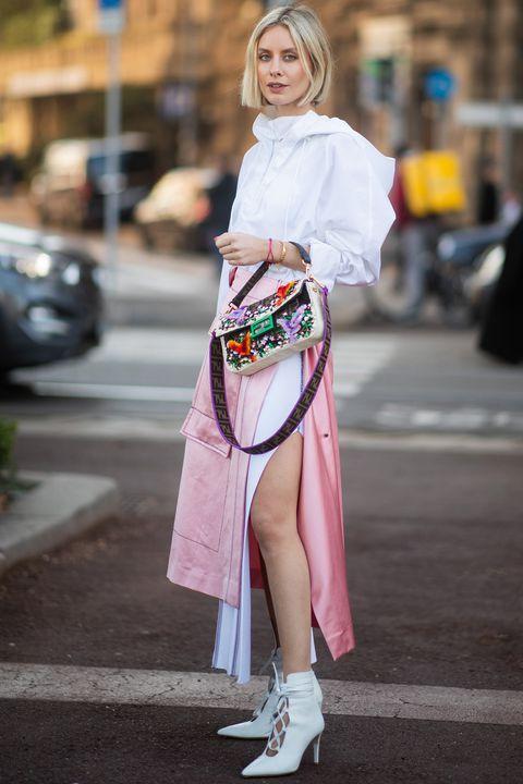 На девушке белая тонкая куртка, ярко-розовая юбка-миди с карманами и разрезом, белые туфли на шнурках с каблуком и сумка с вышивкой.