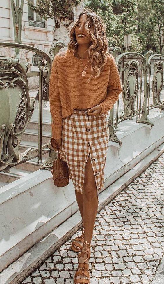 Бледно-оранжевый укороченный свитер в сочетании с клетчатой юбкой с пуговицами и разрезом, бежевыми туфлями с ремешками на шнурках и веревочной сумкой.