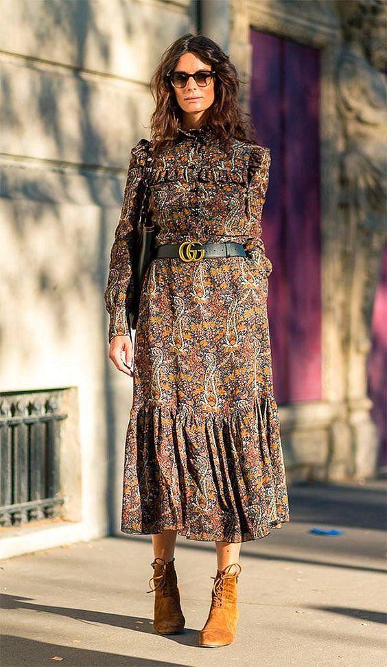 На девушке цветастое платье-миди с рюшами и поясом, замшевые коричневые туфли на шнурках, сумка и очки.