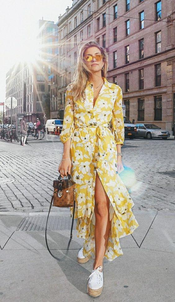 На девушке желтое платье с белыми цветами, воланами и разрезом, белые туфли на шнурках и высокой бежевой подошве, коричневая маленькая сумка и очки.