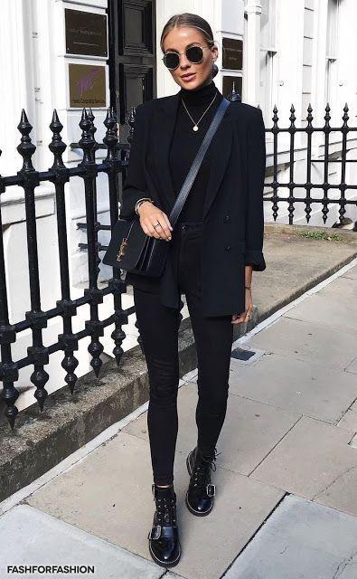 На девушке вся одежда черного цвета: гольф, удлиненный пиджак свободного кроя, джинсы скинни, лаковые ботинки с ремешками на шнуровке, поясная кожаная сумка и очки.