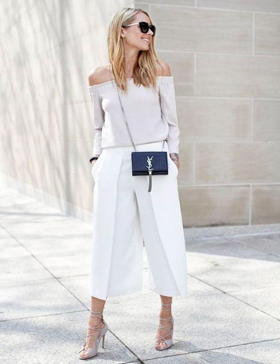 Весь образ создан в белых оттенках: свободная блузка с оголенными плечами, кюлоты длины 7/8, туфли на каблуке с шнуровкой. Лук дополнен черной поясной сумкой и очками.