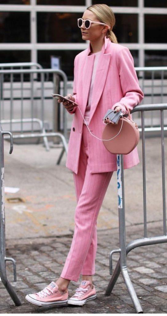 Девушка выбрала розовый брючный костюм в полоску, нежно-розовую круглую сумку, очки  и кеды такого же цвета на шнурках.