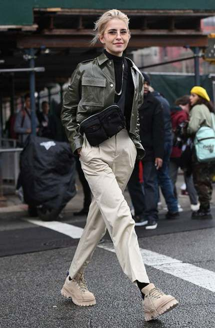 Девушка надела черный гольф,  виниловую темно-зеленую укороченную куртку с карманами, светло-бежевые брюки свободного кроя и такого же цвета ботинки на шнурках с рифленой подошвой. Образ дополнила очками и черной поясной сумкой.