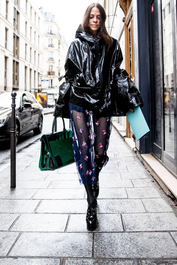 Черный виниловый короткий плащ, темно-синяя полупрозрачная юбка-миди, черные лаковые туфли на шнурках и прозрачная изумрудная сумка.