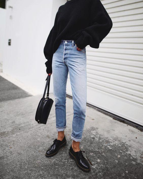 На девушке черный свитер oversize, светло-голубые джинсы прямого кроя, черная кожаная сумка и лаковые оксфорды.