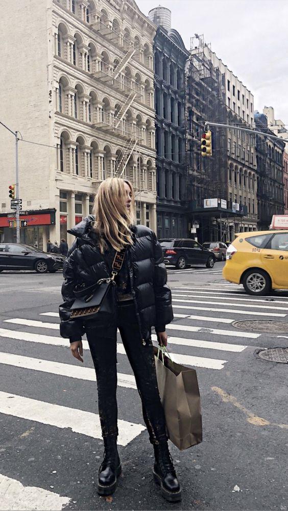 На девушке черная объемная дутая куртка, джинсы скинни, грубые кожаные ботинки на шнуровке и поясная сумка.