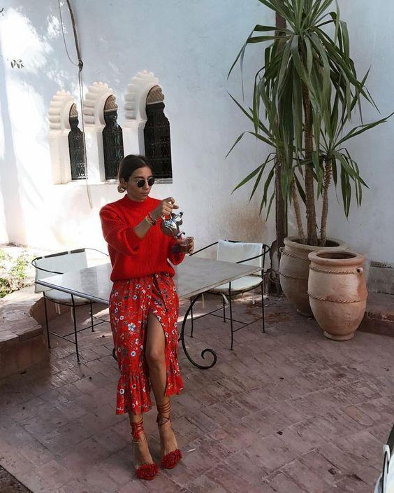 На девушке красный объемный свитер, такого же цвета юбка-миди с разрезом, воланами и цветочным принтом, темно-красные открытые туфли с цветами на носках и шнуровкой на щиколотке.