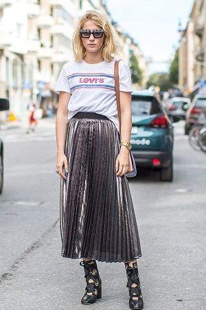 Белая футболка с надписью, юбка-плиссе длины миди в сочетании с кожаными туфлями на шнуровке с широкими лентами. Образ дополняют очки и поясная сумка.